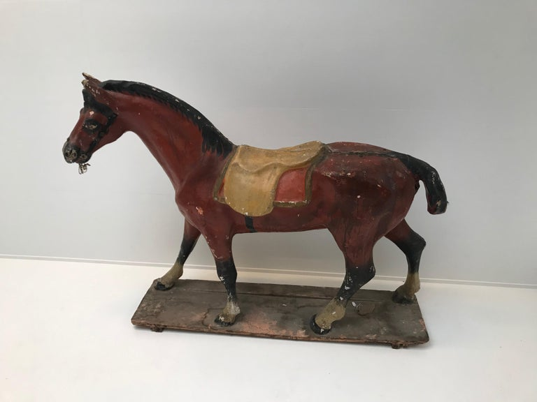Papier mâché horse, with a nice colored patina on a wooden base.