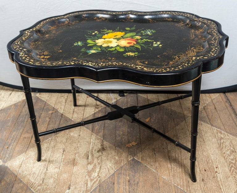 A shaped black papier mâché tray with inlays of mother of pearl around the outer raised edge. Worn gilt decoration within the outer edge of the tray area. The center with hand painted flowers and leaves. Raised on a custom made