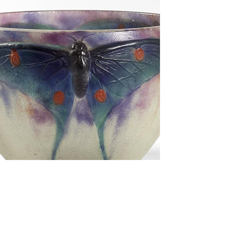 """A French Art Nouveau pâte de verre """"Papillon"""" bowl by Gabriel Argy-Rousseau. The bowl has three Luna moths with brown bodies and textured green wings with red spots. They sit just below the bowl's rim in a background of mottled purple and pink,"""