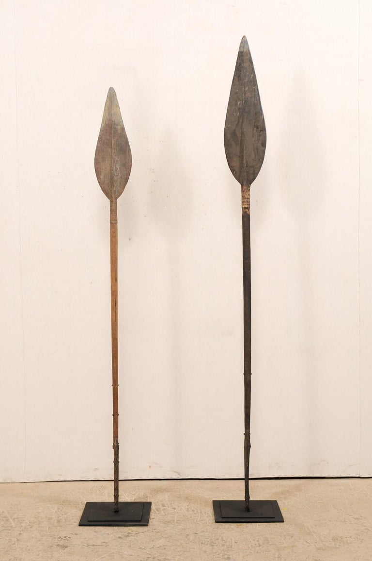 A pair of vintage Papua New Guinea carved wood canoe steering paddles on custom stands. This pair of carved wood paddles originate from along the Sepik river regions of Papua New Guinea. These river and oceanic pieces have spear-like tips at one