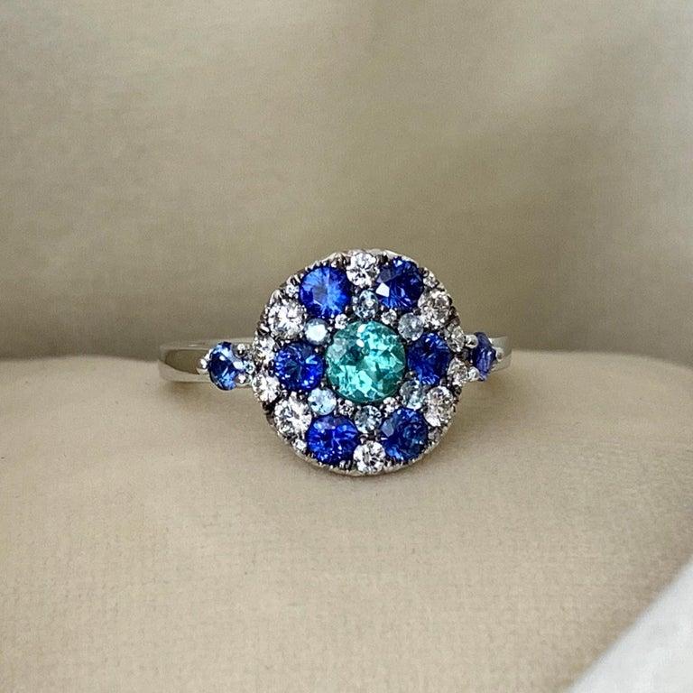 One of a kind ring handmade in Belgium from jewellery designer Joke Quick, in 18K White gold 8,6 g. Set with a Paraiba Tourmaline centerstone 0,41 Carat., Royal Blue Sapphires 0,85 ct.,  Aquamarine 0,07 ct., White brilliant-cut diamonds DEGVVS 0,30