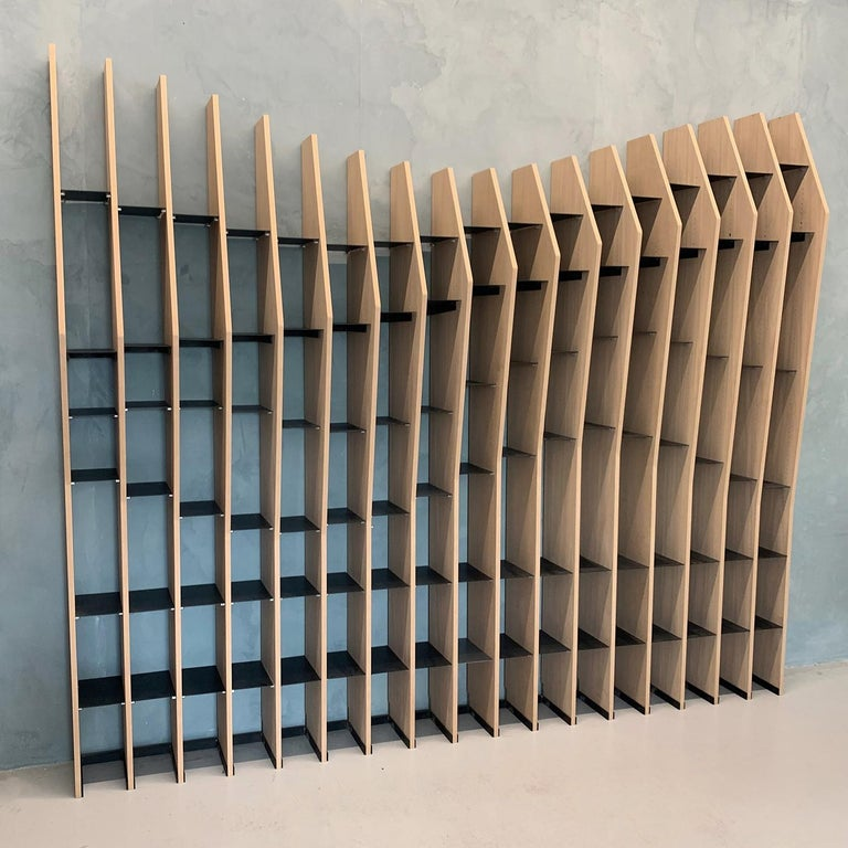 This visually striking, geometric bookshelf is defined by its extremely dynamic appearance, adding a touch of energy and movement to any environment. It is perfect for a home, hospitality environment or business, and can be used to divide an open