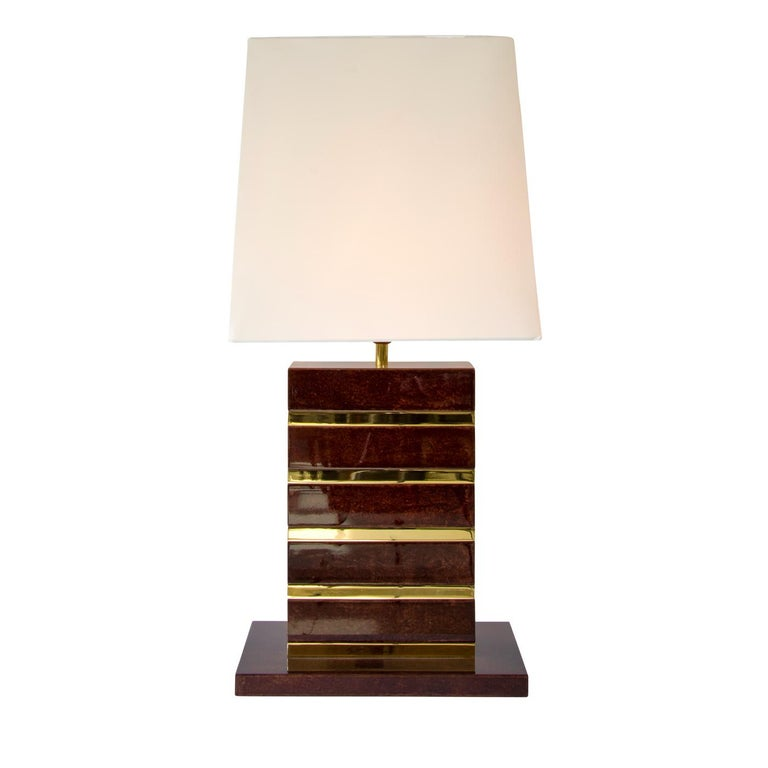 This sophisticated table lamp will be the highlight of any contemporary style decor in your living area or lounge room. The lamp is covered in mocha colored parchment with precious detail in stainless steel and features a high gloss finish. The wide