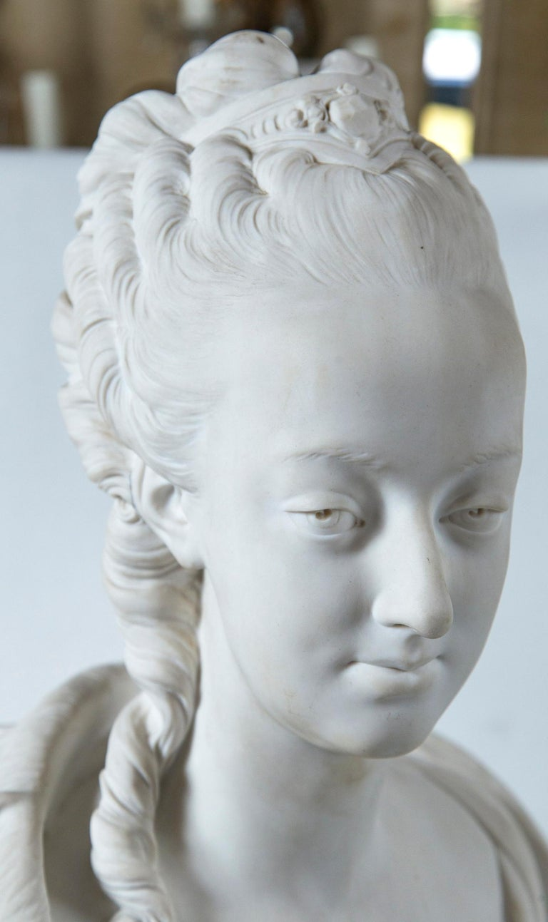 Possibly a bust of Madame du Barry. Signed across the back Pajou. A round seal next to the signature is inscribed Nationale Sevres Manufacture, with letters and number below. There is noSèvres mark that we can find. She wears a outer garment that