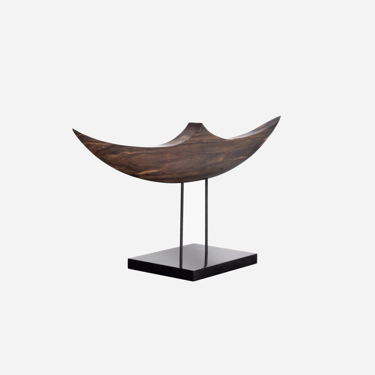 Ebony is a dense hardwood with a rich dark color and finely textured with a smooth surface when polished. This hand carved and shaped sculpture brings out the natural beauty of the wood's graceful structure. This boat shaped sculpture with graceful