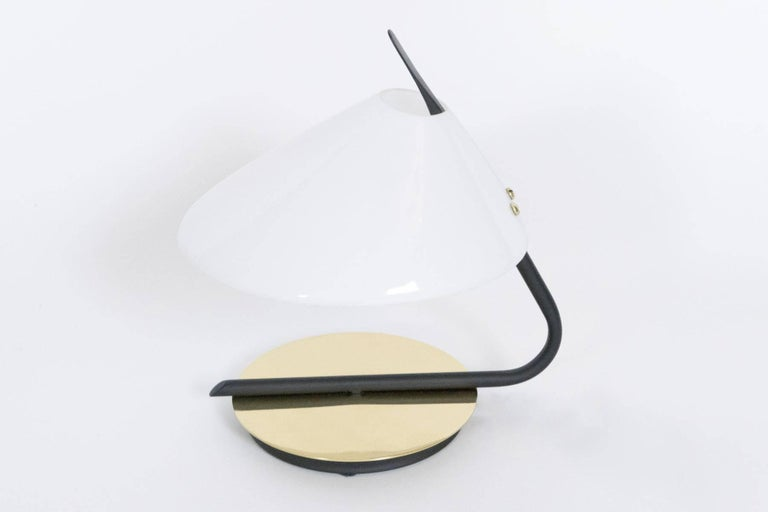 This small-scale lamp enhances shelves, small side tables or it fits about anywhere. The soft light which is diffused by the acrylic shade is accented by the reflection from the brass base.