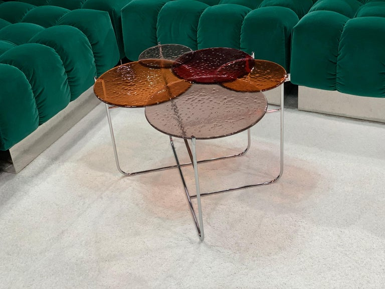 Pastille / side tables by Sebastian Herkner are suspended drops of coloured glass which found their inspiration in the particularity of the glass fusing technique. Through the process the perfectly cut glass circles are transformed: their contours