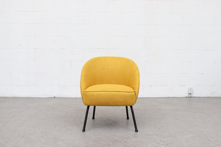 Sweet little chair in new sunshine yellow upholstery with black enameled metal legs. Small stature, frame in original condition with some signs of wear.