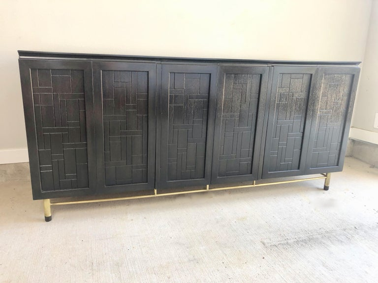 Patchwork credenza / dresser by John Stuart. Newly refinished ebonized wood with brass legs. Tons of drawers for maximum storage.