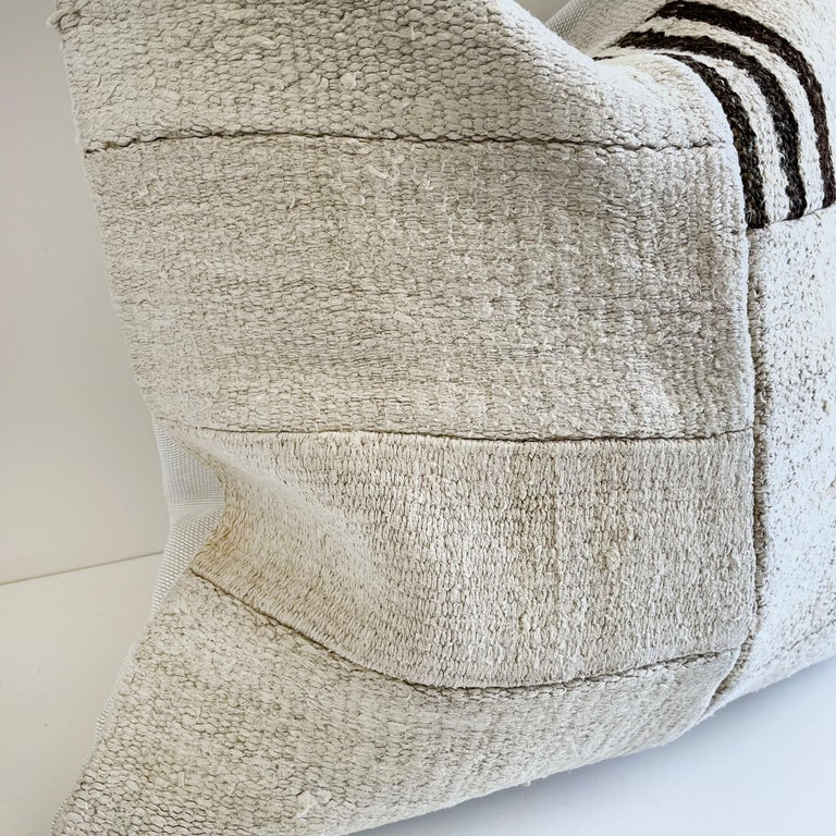 Creamy white hemp rug with brown and natural patchwork style. Unique patchwork pillow has been made with parts of different Turkish rugs, in multiple white tones, and some with stripes. The face is fully lined, with a coordinating backing in a solid