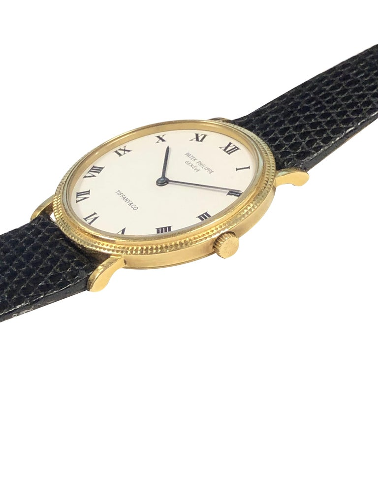 Circa 2005 Patek Philippe for Tiffany & Company Classic Calatrava Reference 3954 Wrist Watch, 33 M.M. 18K Yellow Gold 2 Piece case with Hobnail Bezel, Quartz Movement, White Dial with Black Roman Numerals. New Black Lizard Strap with Original Patek