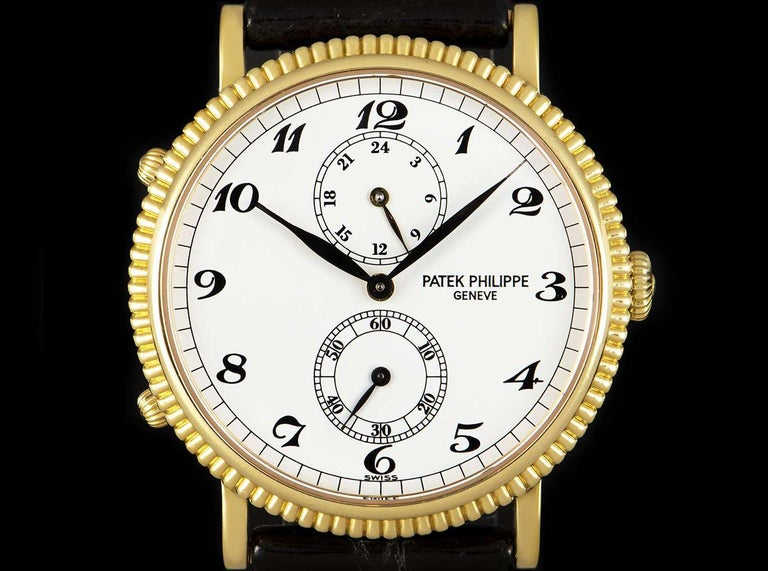 An 18k Yellow Gold 34mm Calatrava Travel Time Men's Wristwatch, white dial with arabic numbers, small seconds at 60'clock, 24 hour indicator at 120'clock, a fixed 18k yellow gold reeded bezel, an original black leather strap with an original 18k