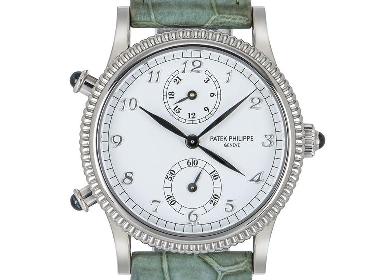 A 29 mm Calatrava Travel Time with complications in white gold by Patek Philippe. Features a white Arabic dial with a second-time zone hand, a 24-hour display and a small seconds display concealed by a white gold reeded bezel.APatek Philippe green