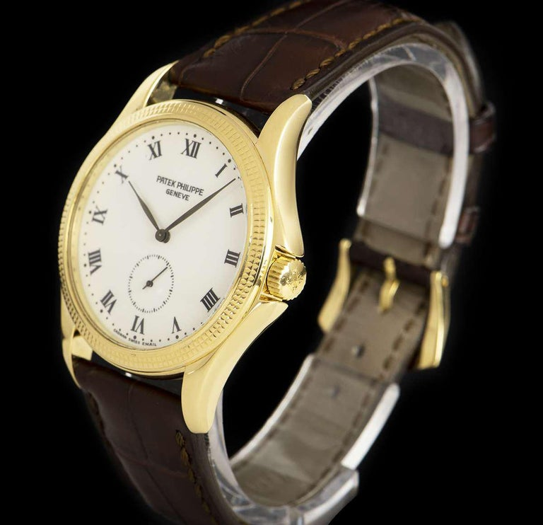 An 18k Yellow Gold Calatrava Gents 35mm Wristwatch, white enamel dial with roman numerals, small seconds at 6 0'clock, a fixed 18k yellow gold hobnail patterned bezel, an original brown leather strap with an original 18k yellow gold pin buckle,