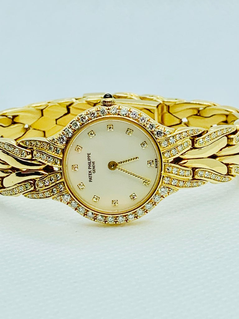 Gorgeous Patek Philippe la Flamme 21mm ladies Quartz watch! This piece is in 18K yellow Gold and features a mother of pearl dial and diamond bezel, as well as diamonds in the band and number markers. The watch has a total of 144 diamonds that are
