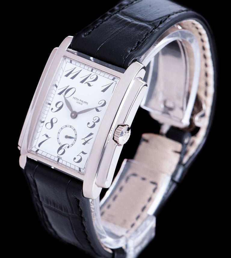 An 18k White Gold Gondolo Gents Wristwatch, white porcelain dial with arabic numbers, small seconds at 6 0'clock, a fixed 18k white gold bezel, a black leather strap (not by Patek Philippe) with an original 18k white gold deployant clasp, sapphire