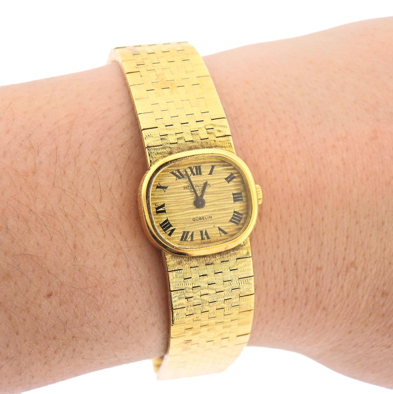 Vintage 18k gold Patek Philippe for Gubelin lady's watch. Case measures 20mm x 18mm, with gold ribbed dial, signed by Patek Philippe and Gubelin. Bracelet is 6