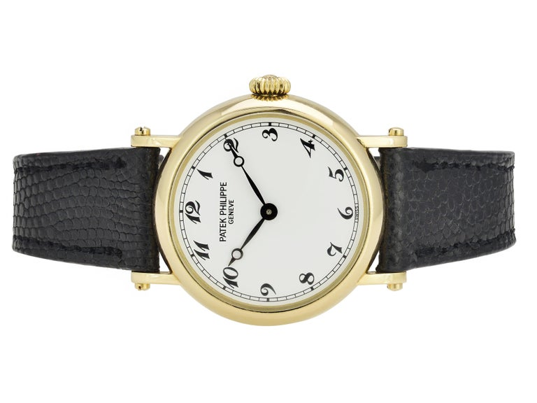 18 Karat Yellow Gold Patek Philippe Ladies Calatrava Wristwatch on Black Leather Strap.  Reference 4860 Manual Wind Movement. 26mm Case with White Dial and Arabic Numerals. 18 Karat Yellow Gold Tang Buckle. Includes 1 year warranty on timekeeping
