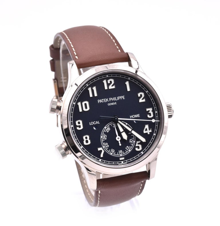 Movement: automatic Function: hours, minutes, seconds, date, dual time zone and day/night indicator Case: 42mm round case, sapphire protective crystal, push/pull crown Dial: black dial, arabic numbers Band: brown Patek Philippe leather strap with