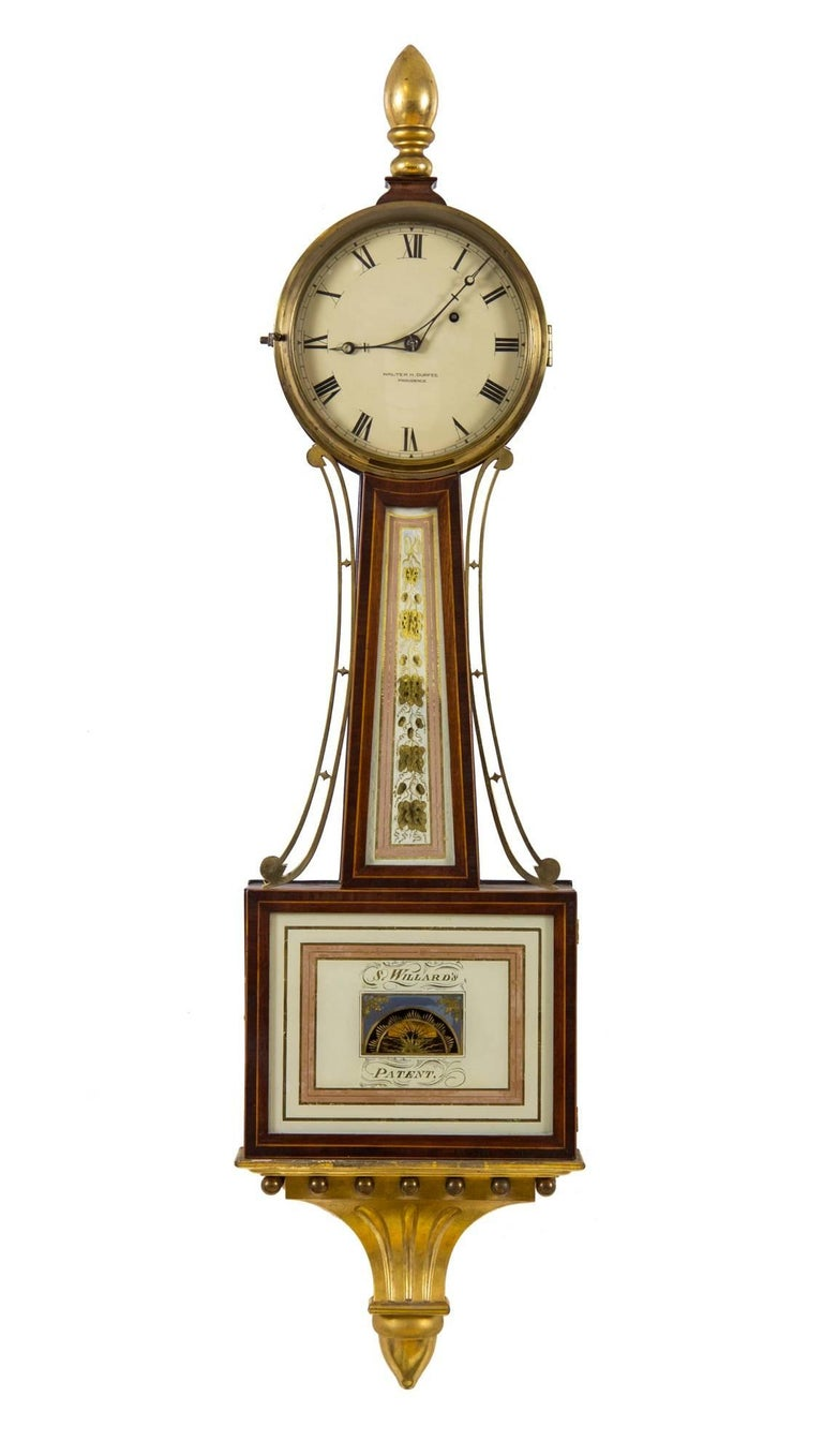 In the world of American banjo clocks, Walter Durfee produced the finest reproductions of the famous Willard timepiece. Durfee was a perfectionist and his hand is seen throughout the choice and quality of painting, wood, etc. The gold leafing is of