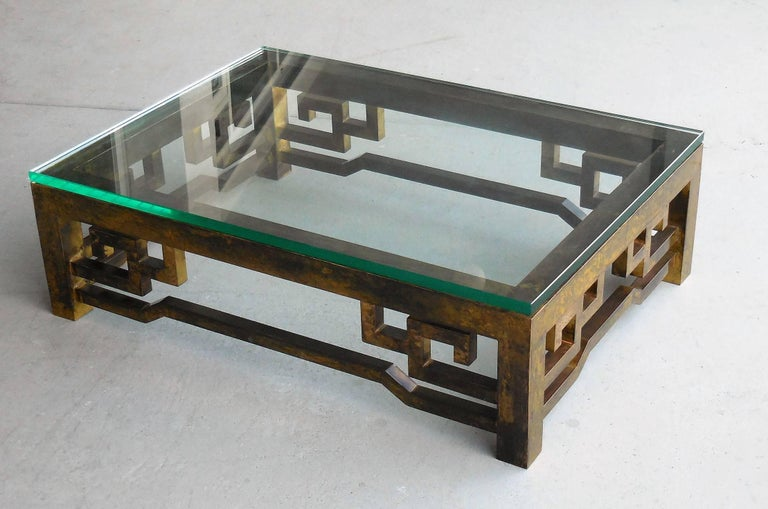 A low brass coffee table with thick glass top. Very beautiful patina on this table.