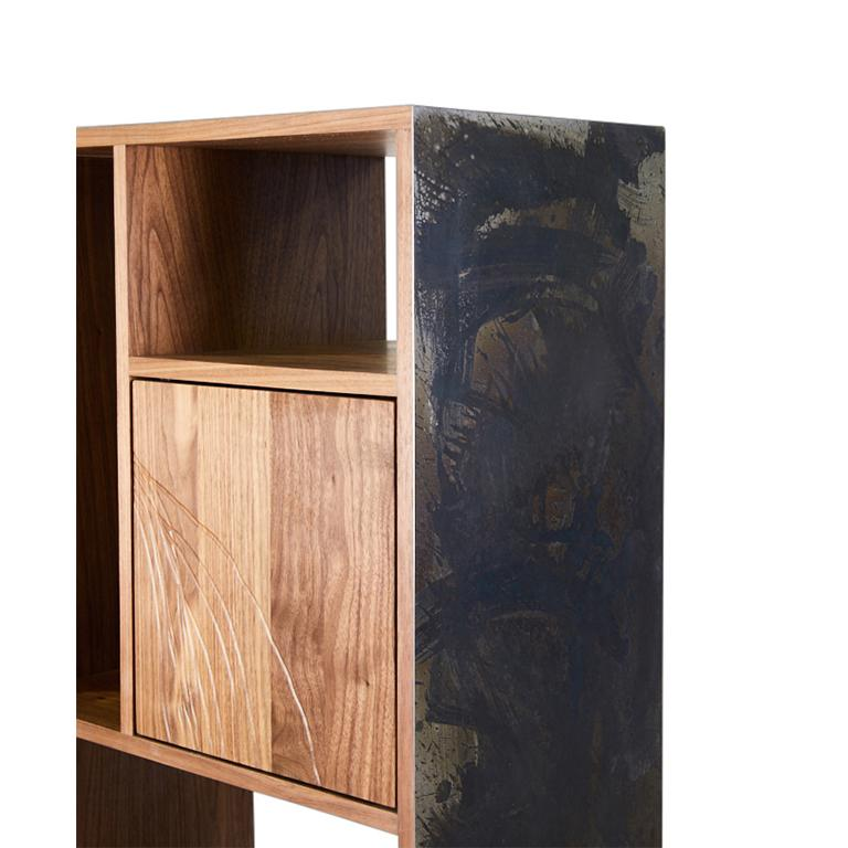 The E-1 is a dynamic étagère constructed from Walnut wood with a flame treated and patinated steel exterior. Three compartments, two doors and one drawer, feature Walnut wood faces with abstract line drawing etched into the wood. All hardware is