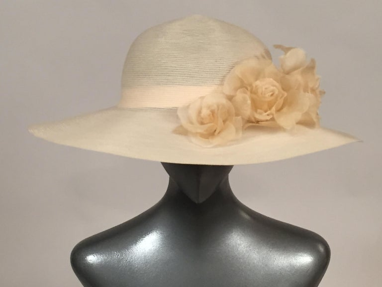 An elegant cream net hat from Patricia Underwood is trimmed with three graduated silk roses in a slightly deeper shade. The hat has an interior grosgrain ribbon hatband and the label is attached. It is in excellent condition. Measurements; Height