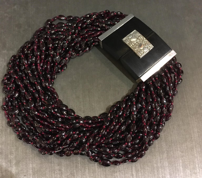 Hand strung garnet beads on silk thread with large decorative ebony and sterling clasp. Artist signature on clasp. Can be worn straight so it sits lower on neck, or beads can be twisted so it sits higher on the neck. Looks beautiful either way.