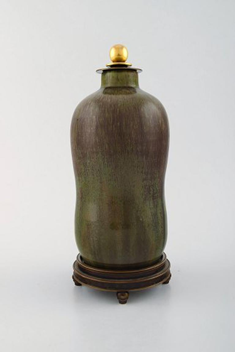 Patrick Nordstrøm / Carl Halier for Royal Copenhagen, lidded stoneware vase with bronze foot and bronze lid by Knud Andersen (Denmark). 1930s-1940s. Beautiful glaze in green and brown shades.