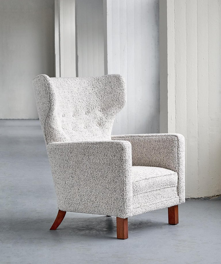 This rare armchair was designed by Paul Boman and produced by his company Oy Paul Boman AB in Finland in the 1940s. The design offers a nice contrast between the curved lines of the high winged back and the straight lines of the armrests. The