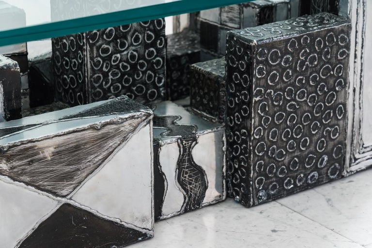 A popular form that Paul Evans would revisit through his career is a composition he called Skyline. Skyline pieces, such as this unique, playful low table, were comprised of individually hand-welded boxes of varying heights, shapes, textures and