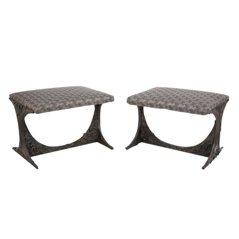 """Sculpted bronze benches by Paul Evans. Pair of sculpted bronze benches with a gray black patterned upholstered seat cushions. Model number: PE-112. Both benches signed """"PE 69"""" on in the corner of each cross stretcher. Minor discoloration to the"""