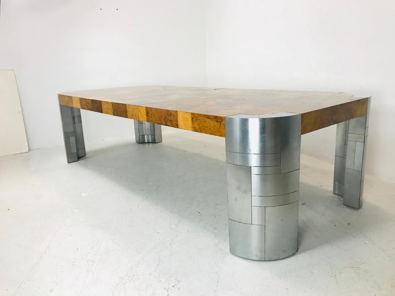Large, commanding patchwork burl wood dining table with thick chrome legs. Includes 2 leaves that measure 14.75