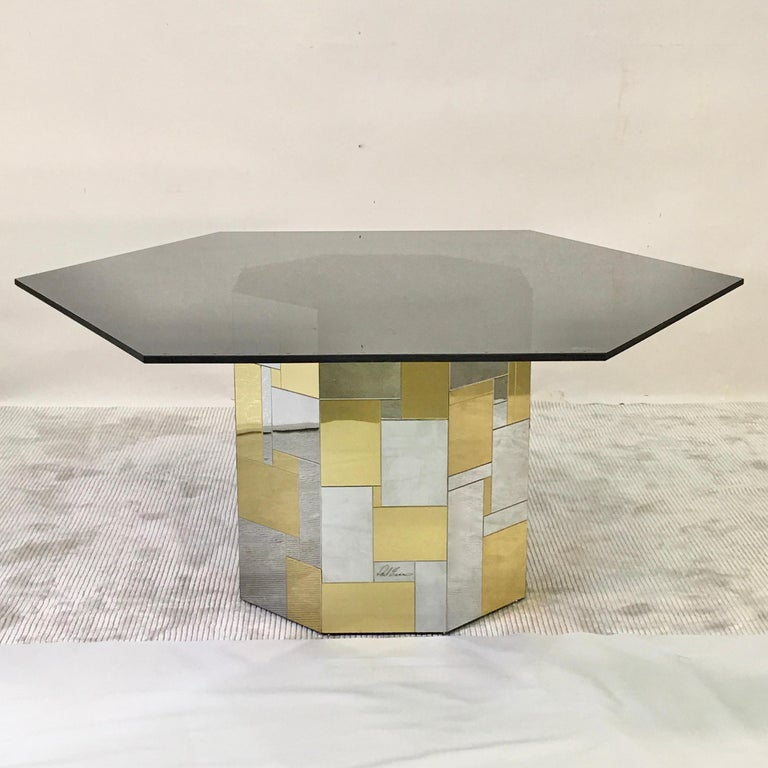 Hexagonal smoked black glass top on a signed Paul Evans brass and chrome patchwork tiled octagonal pedestal drum base.  From his Cityscape Collection for Directional, 1972. Total height 25 inches. Pedestal base alone is 24.5 inches high by 22.25