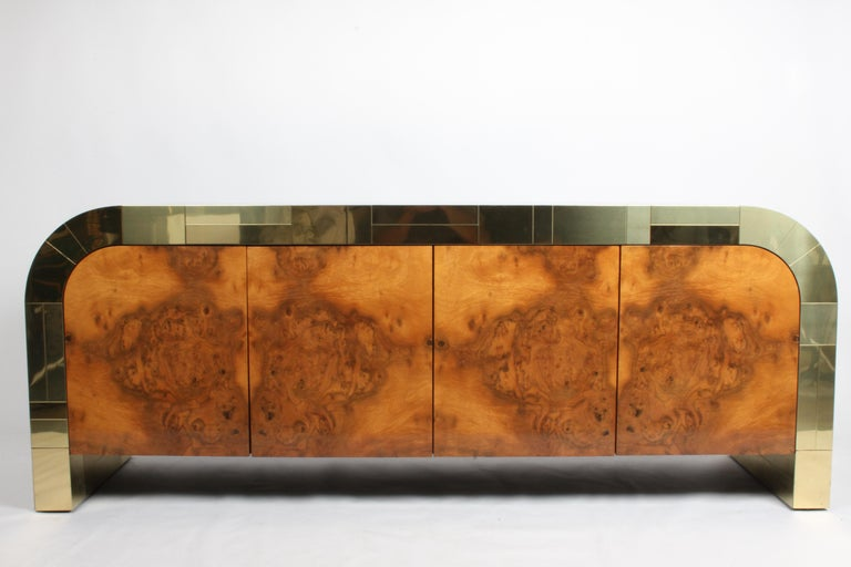 Rare 1970s Paul Evans Cityscape sideboard with waterfall ends for Directional with brass tiles and book matched Burl wood doors. Interior laminated in black with adjustable shelves, right side has two drawers , top one is divided. Minor wear and