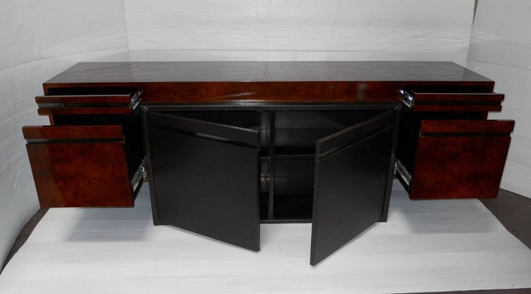 An amazing Paul Evans credenza or buffet. Made for Directional. Have four drawers and two center doors. Central section is covered in leather and has one interior shelf. Drawers have a strip of brushed steel for detail and float on either side of