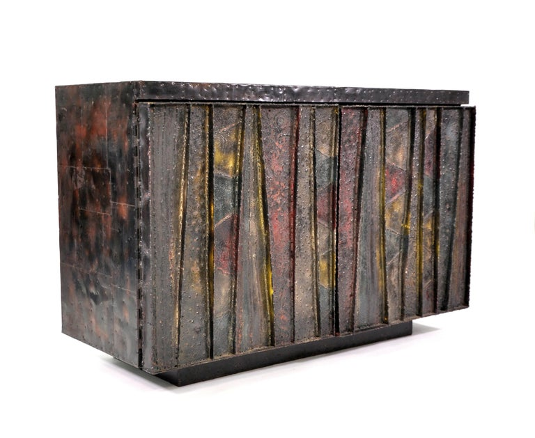 A 1960s Paul Evans Studio for directional deep relief Brutalist credenza or bar cabinet with welded, patinated and polychromed steel doors in hues of red, gold, blue-green and bronze. The sideboard has nailed-on dark patinated bronze patchwork