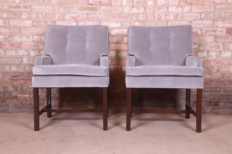 A gorgeous pair ofMid-Century Modern club chairs or dining armchairs  By Paul Evans for Directional  USA, 1960s  Tufted gray velvet upholstery, with walnut legs and stretchers.  Measures: 23.5