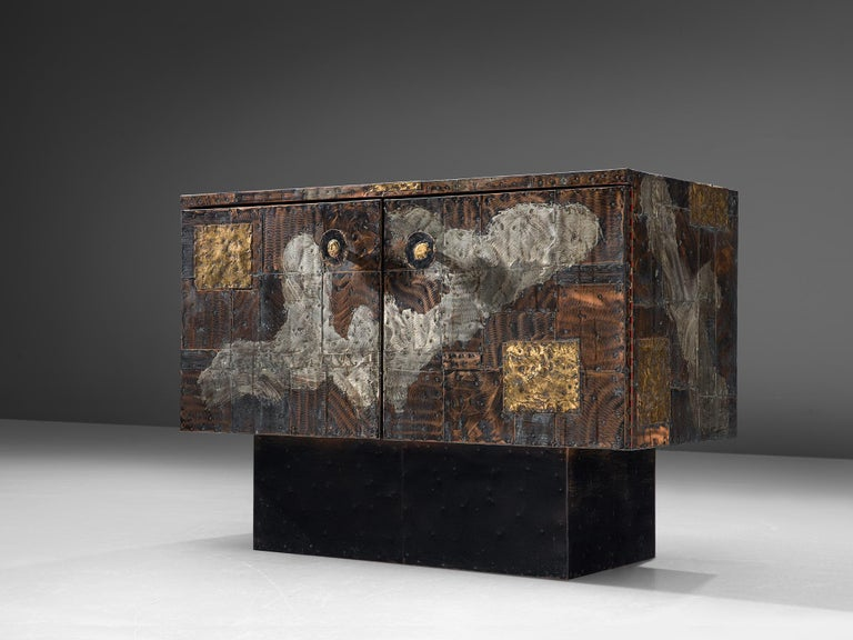 Paul Evans Studio for Directional, patchwork cabinet model PE-302, patinated copper, steel, brass, slate, United States, circa 1960.  Raw and robust small sideboard designed and produced by Paul Evans for Directional furniture. The wheeled