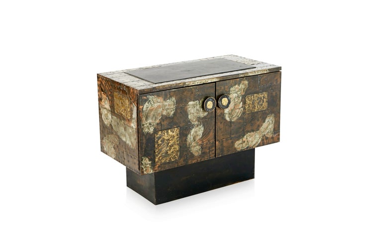 Stunning copper clad cabinet by Paul Evans for Directional, produced in 1967. This incredible piece of design history is fabricated from patinated pieces of copper, brass, and pewter which have been welded and nailed in a patchwork style pattern