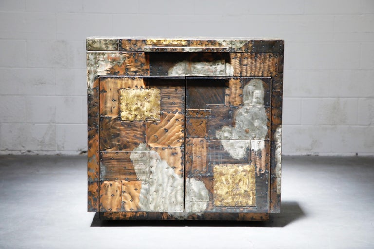 This rare patchwork copper flip topdry bar by Paul Evans was crafted in the mid-1960s by Directional. A collectors item and piece of design history, this stunning liquor cabinet was handcrafted with patinated pieces of copper, brass, and pewter