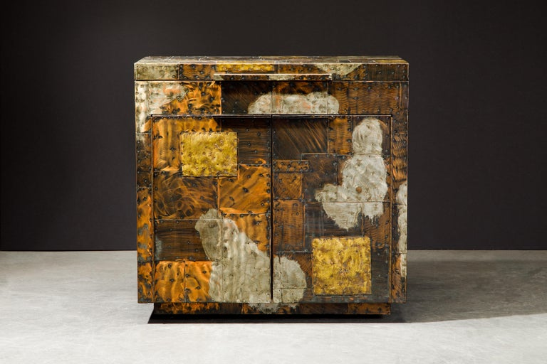 This rarepatchwork copper flip topdry bar by Paul Evans was crafted in the mid-1960s by Directional. A collectors item and piece of design history, this stunning liquor cabinet was handcrafted with patinated pieces of copper, brass, and pewter