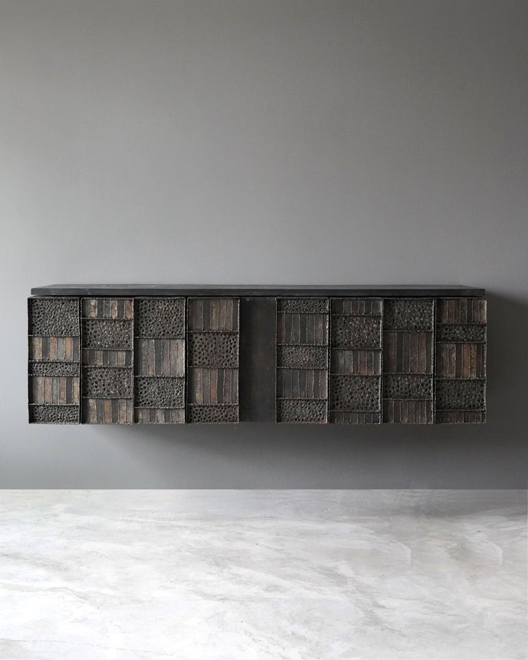 A rare wall-mounted cabinet. Designed and produced by Paul Evans in his studio, New Hope, Pennsylvania, America. Features welded, perforated, and hand-painted steel over wood, original slate top.   Production of this model cabinet started in 1962