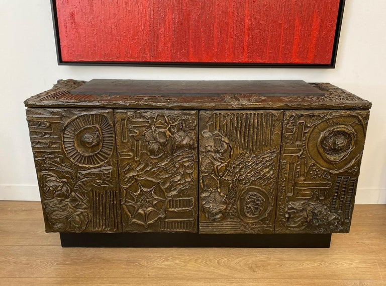 Paul Evans Brutalist sculpted bronze cabinet  Sculpted-bronze series cabinet,  Exceptional abstract forms, solid volumes and powerful brutal shapes, Two bi-fold doors concealing storage with adjustable shelves to each side. One large inset slate