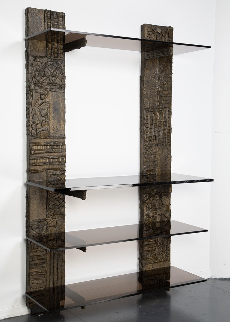 Stunning Paul Evans wall-mounted étagère from the sculpted metal collection for Directional Furniture. The unit features two pilasters supporting four bronze-tinted glass shelves. Pilasters rest on the floor and are mounted to the wall with wood