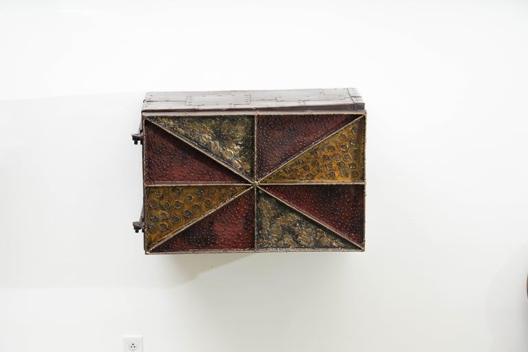 Despite the accessible size and lively surface decoration, very few of this style cabinet were produced by the Paul Evans Studio. With the same welded steel frame in a radial diamond pattern and patchwork steel sides, each were individually