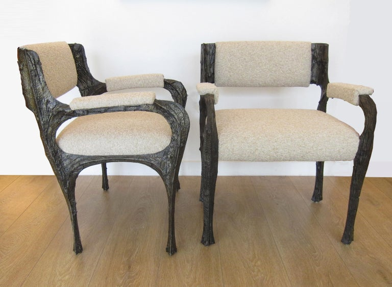 Paul Evans set of twelve brutalist sculpted bronze dining chairs. This extremely rare to find set is comprised of two armchairs (Model PE 105) and ten side chairs (Model PE 106). Newly upholstered with a heavy bouclé fabric. References and