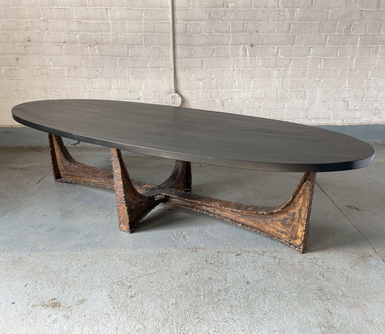 A rare Paul Evans coffee table with an elliptical slate top and a welded and patinated steel base, produced by Paul Evans Studio circa 1965. The base, with its arched cruciform shape, has an almost bridge-like architectural bearing. The heavy slate