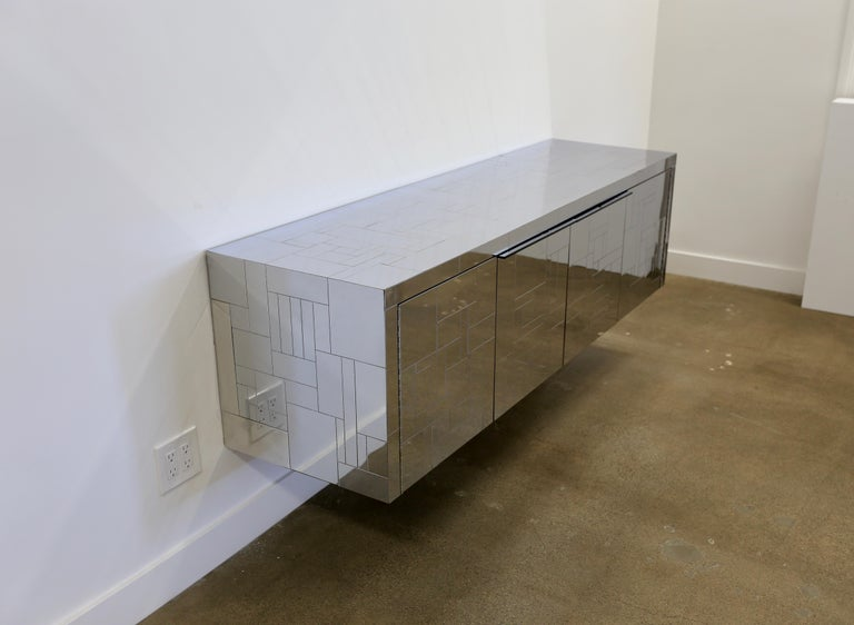 Paul Evans wall-mounted Cityscape cabinet. Manufactured by Paul Evans Studio for Directional, circa 1975. This piece is signed. The chrome-plated steel cityscape detail continues on the bottom of the credenza.