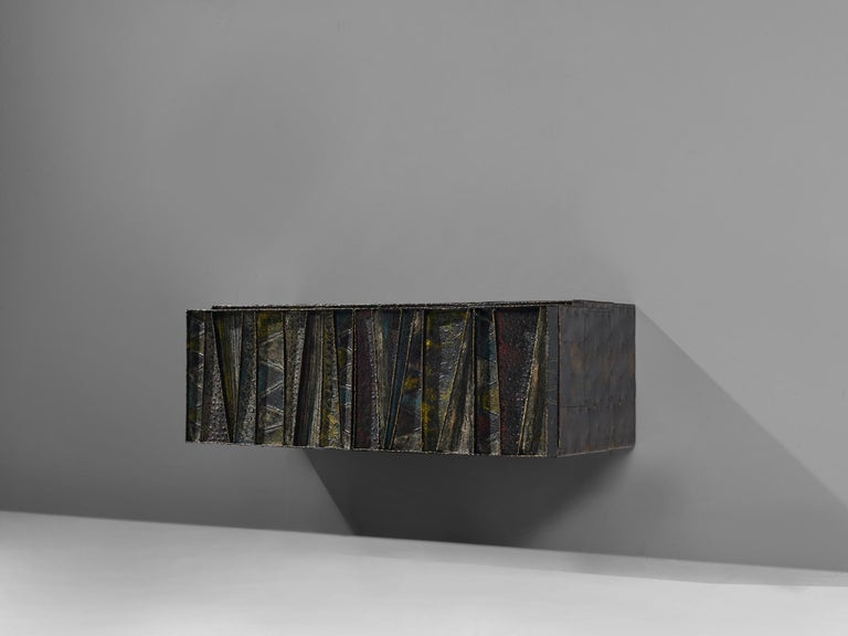 Paul Evans for Paul Evans Studio, deep relief, wall-mounted sideboard model PE-19, welded and patinated steel and darkened wood, United States, circa 1972  Paul Evans 'Deep Relief' wall-mounted cabinet with welded and patinated steel doors in